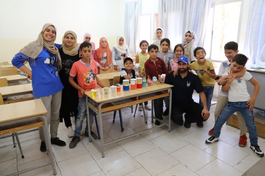Houda con niños huérfanos sirios en clase de ciencias haciendo experimentos