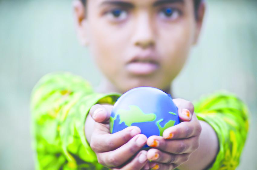 Niño sosteniendo una bola del mundo