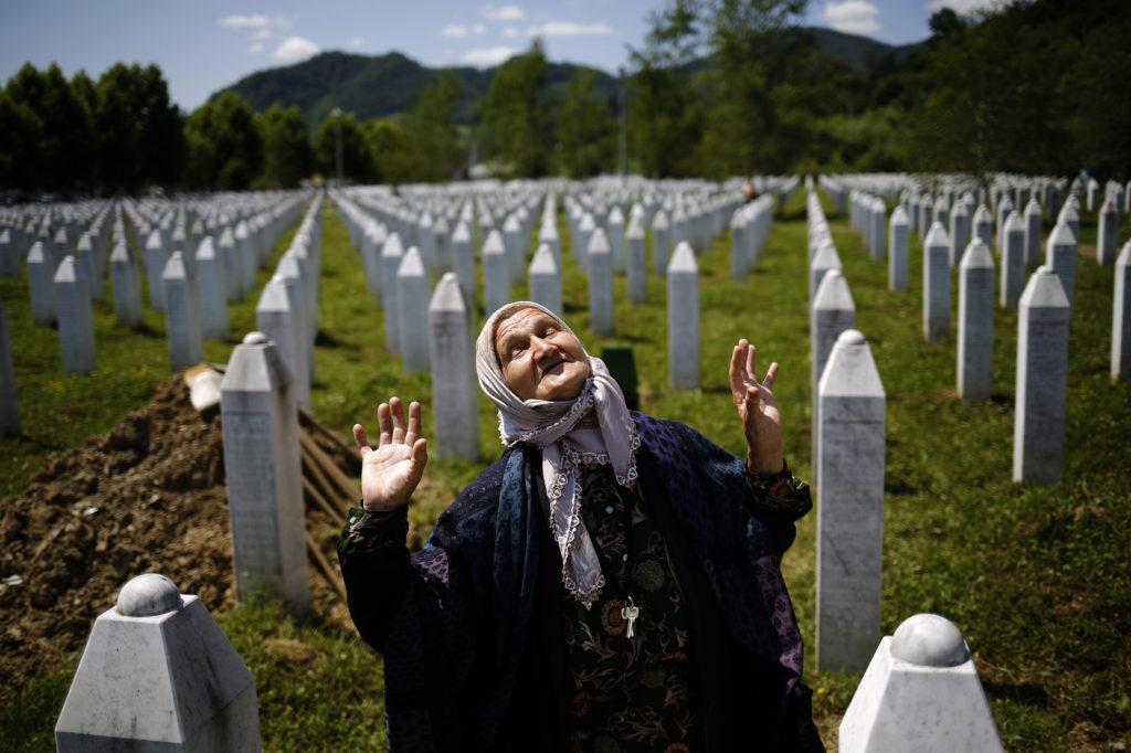La mujer reacciona mientras se para cerca de la tumba de un pariente en el Memorial de la masacre de Srebrenica