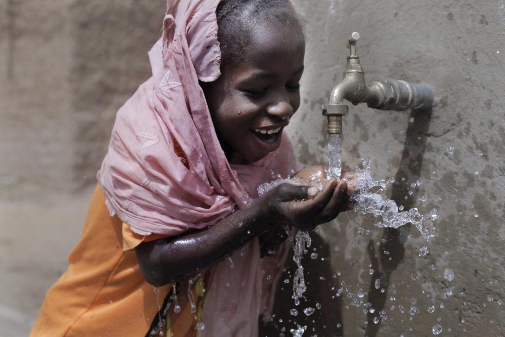 Niña nigeriana bebiendo agua