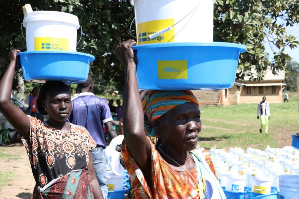 Mujeres en sudán del sur llevando agua y artículos de higiene