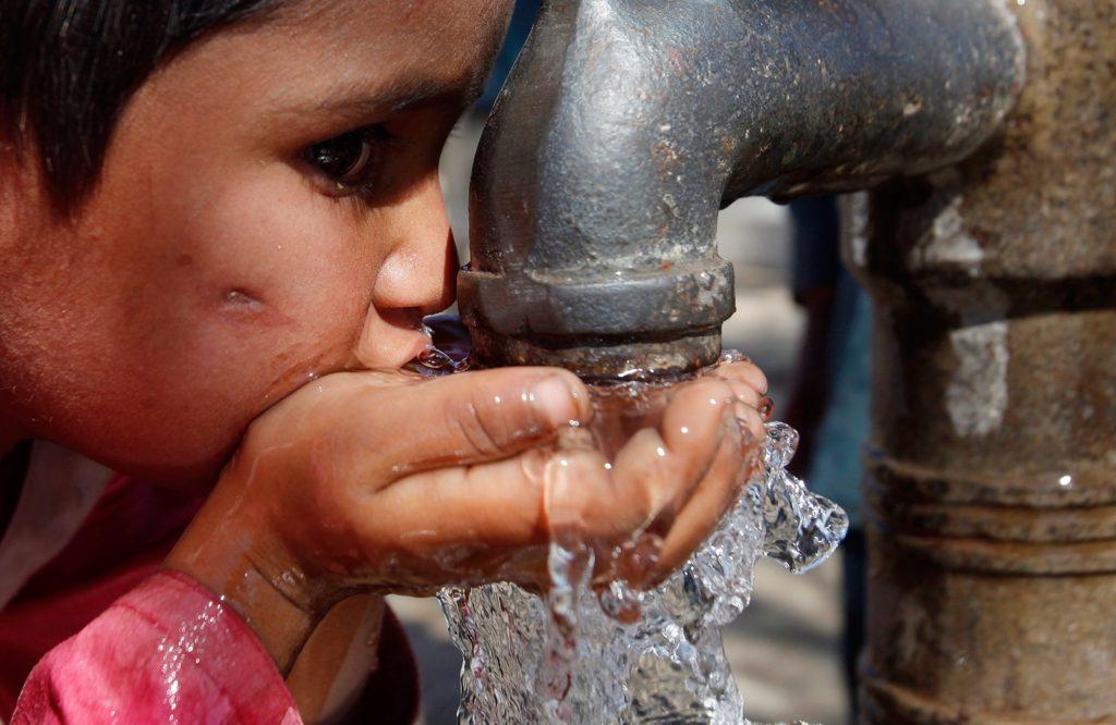 Niño bebiendo de una fuente