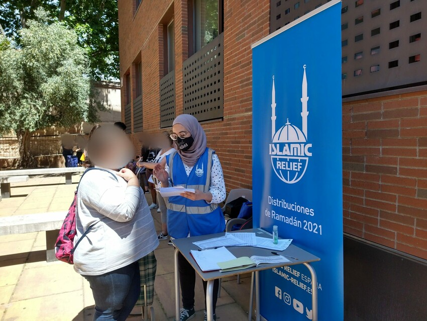 Voluntaria de Islamic Relief entregando un vale de alimentos