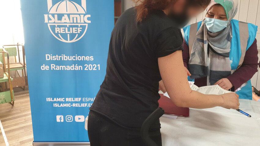 Voluntaria de Islamic Relief informando a una beneficiaria de los vales de alimentos de Ramadán 2021