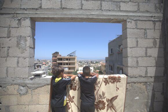 Dos niños de Gaza mirando por la ventana