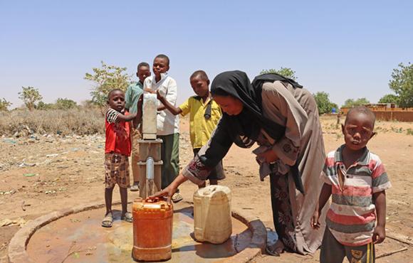 Em Khalthum y su familia llenando garrafas de agua